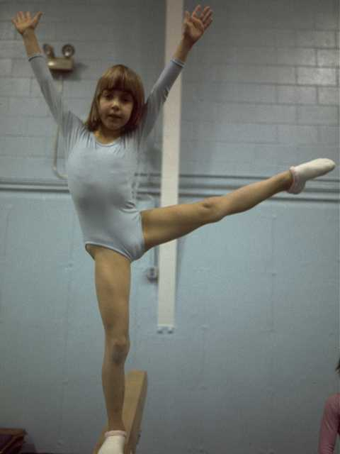 young girl in an exuberant balance pose
