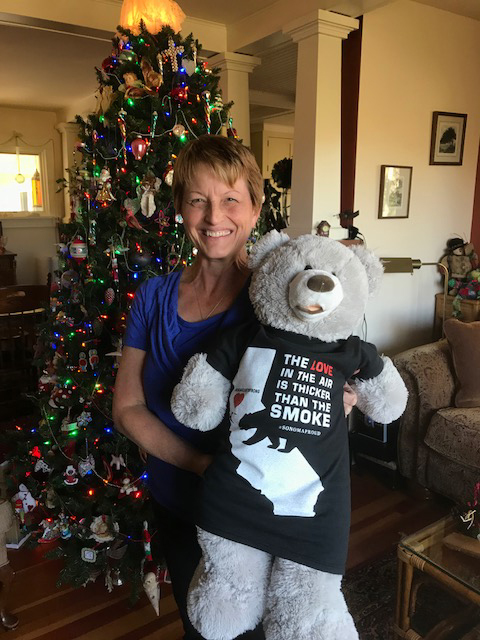 Deborah Myers holding her Sonoma Strong Bear in front of the Christmas Tree