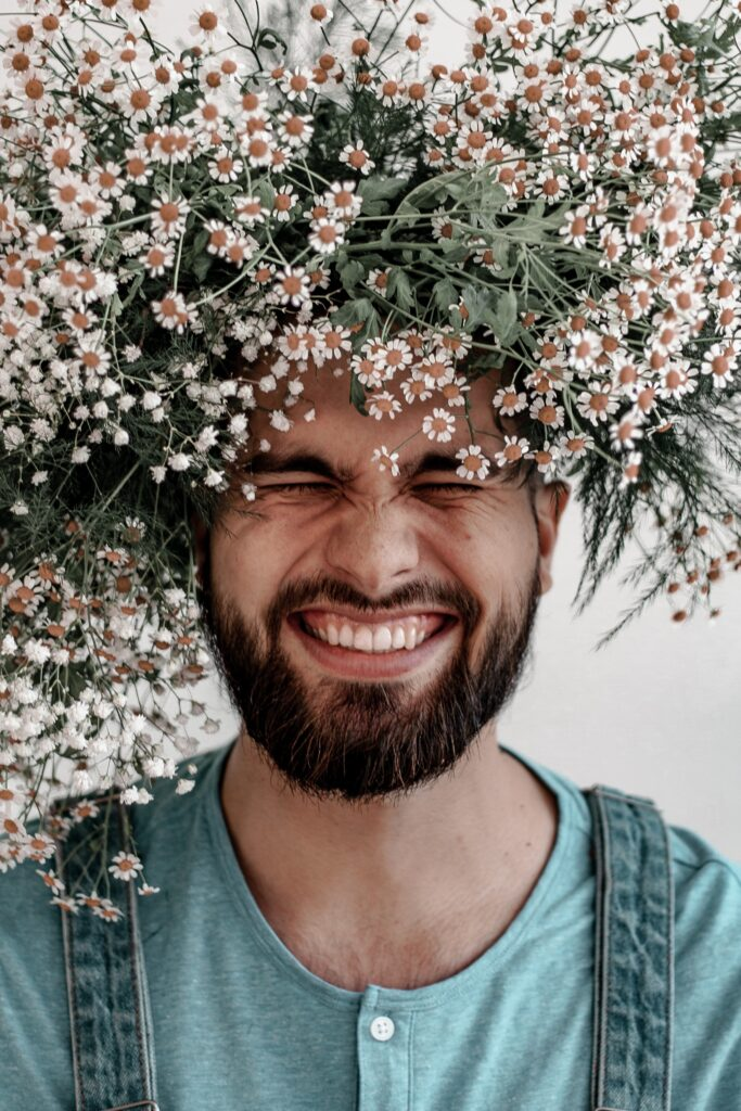 Man smiling, crowned with flowers